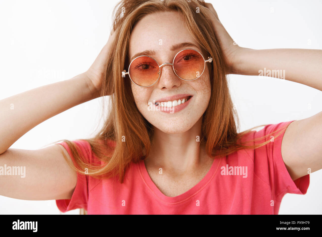 f1a821f3b7a Headshot of creative and happy attractive ginger girl with cute freckles in  stylish pink sunglasses touching hairstyle and smiling broadly enjoying new  look ...