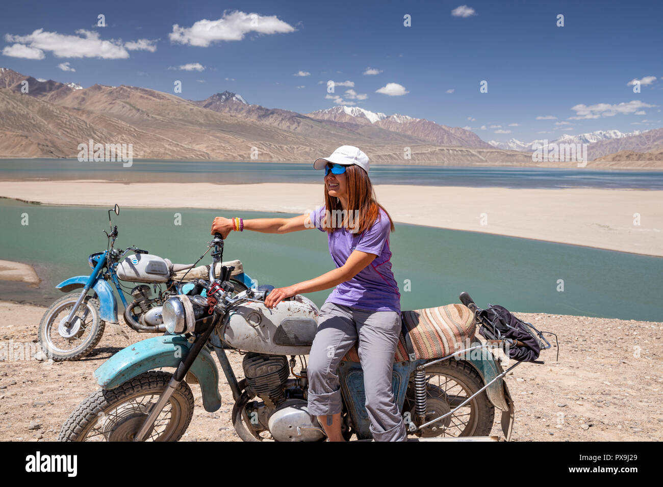 Checking out a couple of old Russian motorcycles parked at Yashikul Lake in the Upper Gunt Valley, Pamir Mountains, Tajikistan - Stock Image