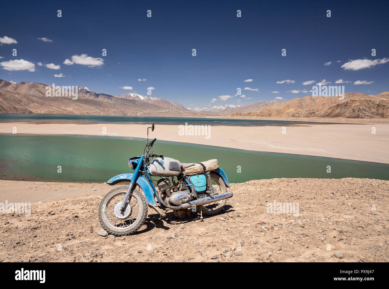 Couple of old Russian motorcycles parked at Yashikul Lake in the Upper Gunt Valley, Pamir Mountains, Tajikistan - Stock Image