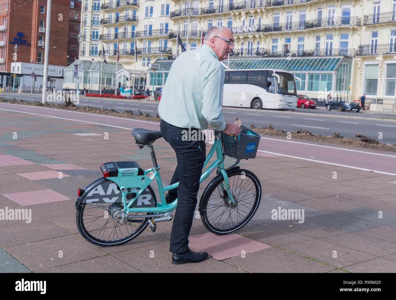 Middle aged man riding a rented / hired rental bicycle in Brighton, East Sussex, England, UK. - Stock Image