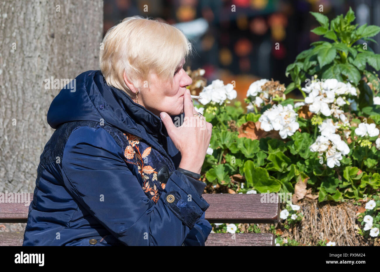 Side view of a middle aged woman sitting smoking a roll-up cigarette in the UK. - Stock Image