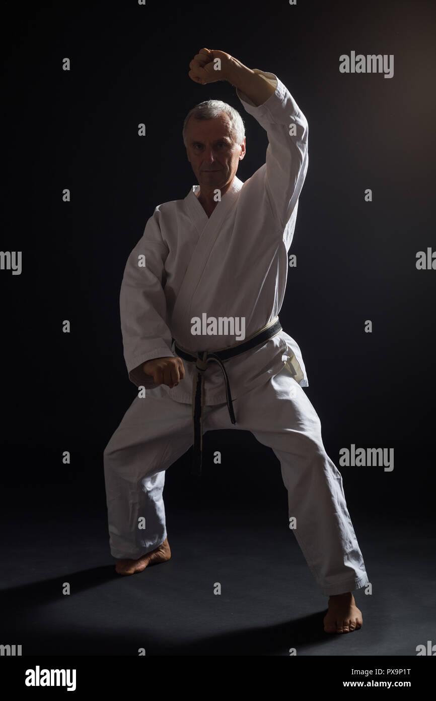 Senior man practicing karate. - Stock Image