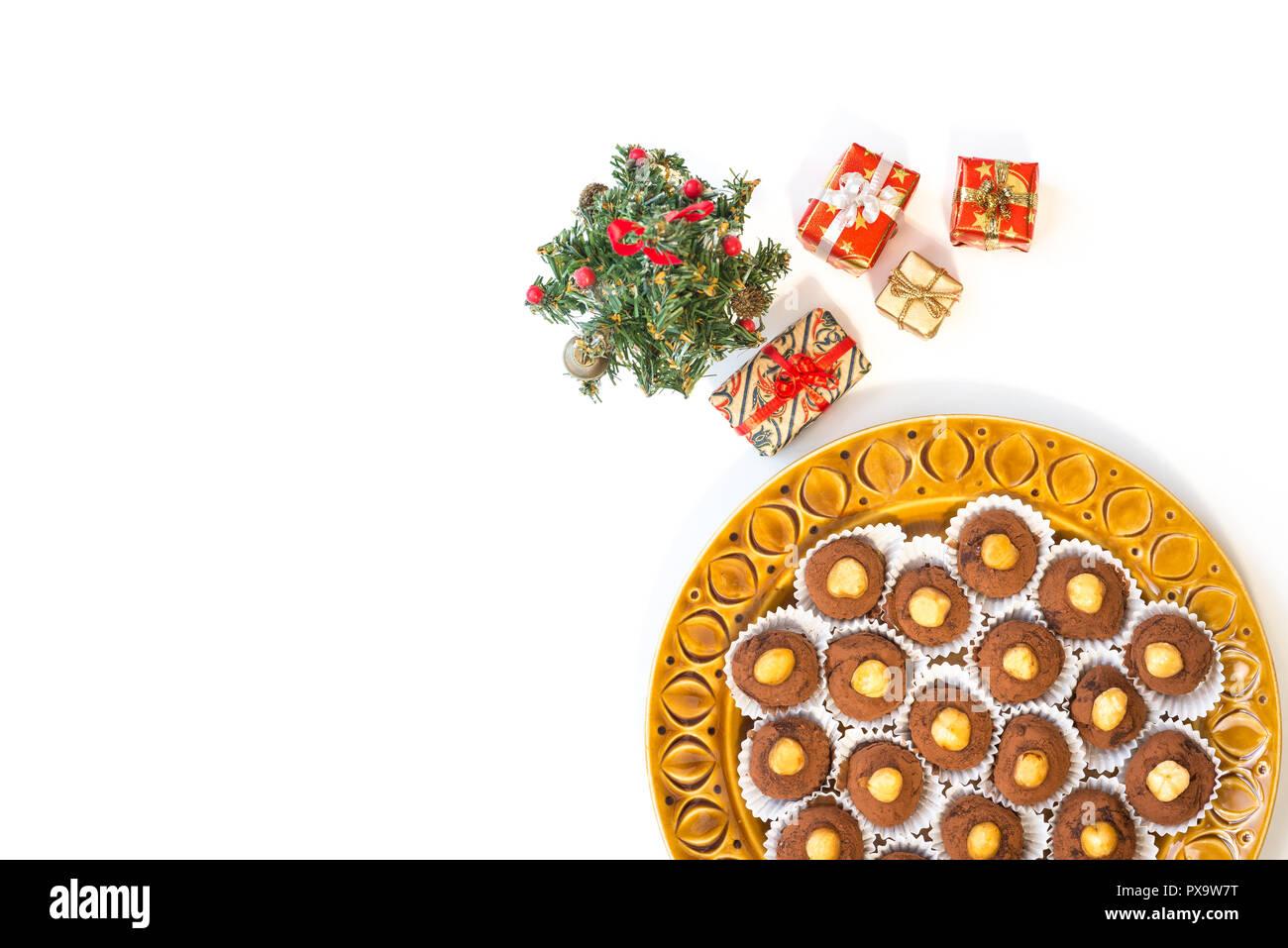Homemade christmas dessert; chocolate bonbons with chopped hazelnuts, white background - Stock Image