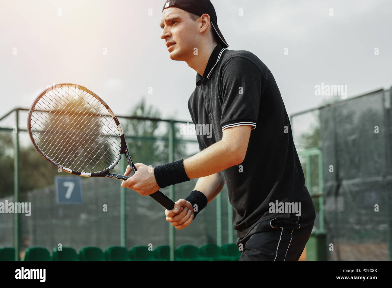 Close up of man holding tennis racket in both hands to straighten strike. - Stock Image