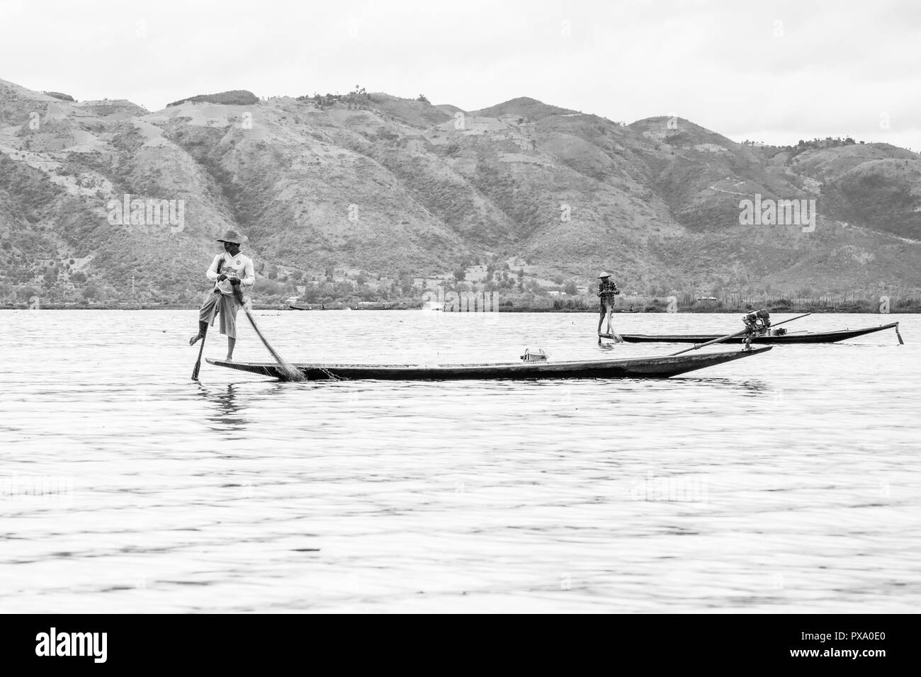 Travel: local young Burmese fisherman wearing Manchester United shirt, balancing and steering boat with his foot in Inle Lake, Burma, Myanmar, Asia - Stock Image