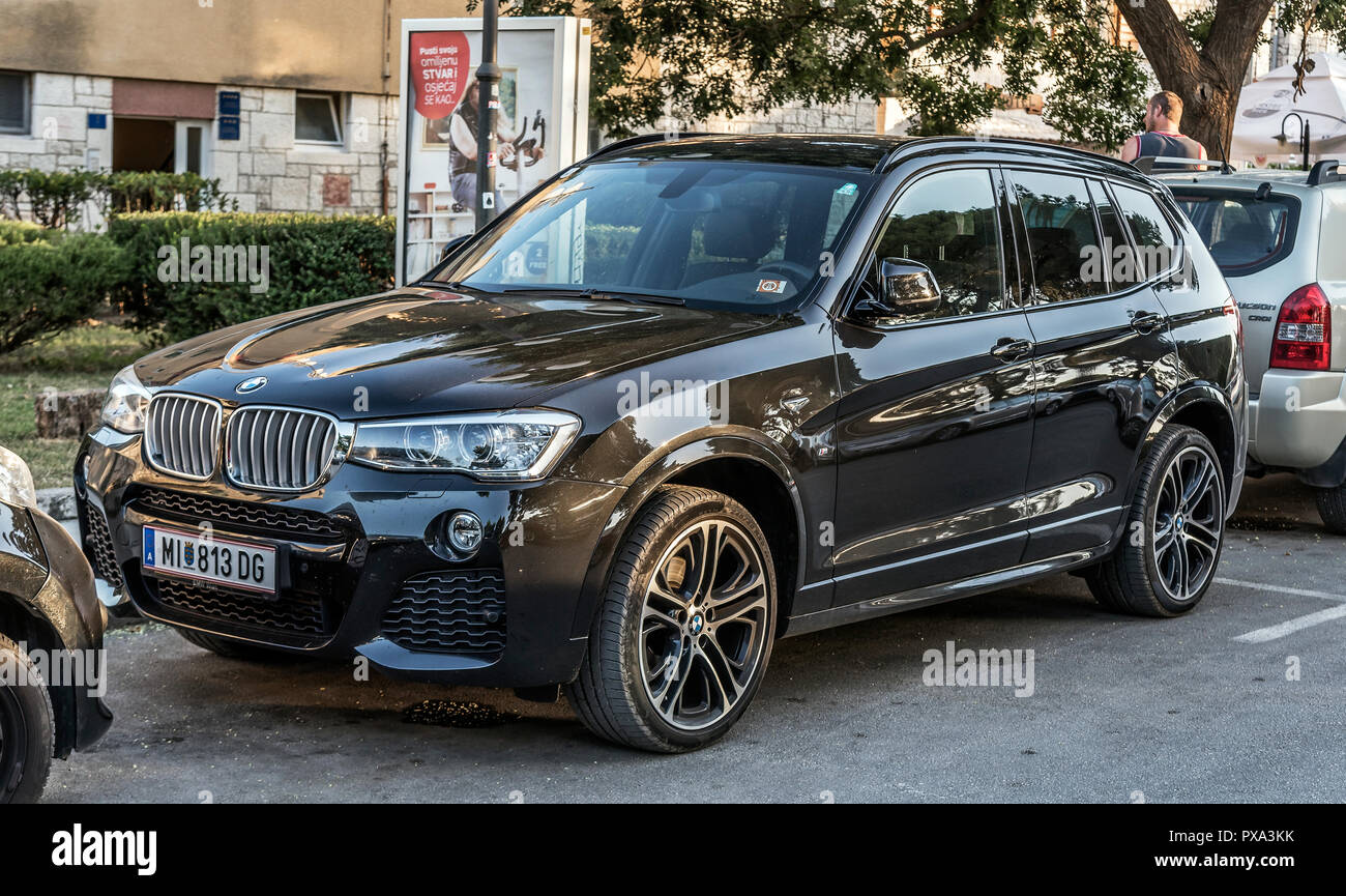 BMW X5 is parked in the city parking. - Stock Image