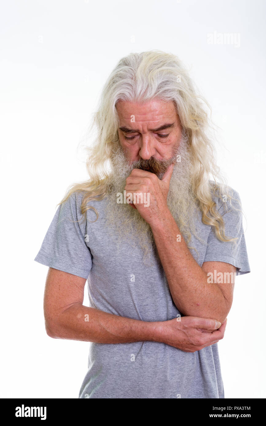 Studio shot of sad senior bearded man thinking while looking dow - Stock Image
