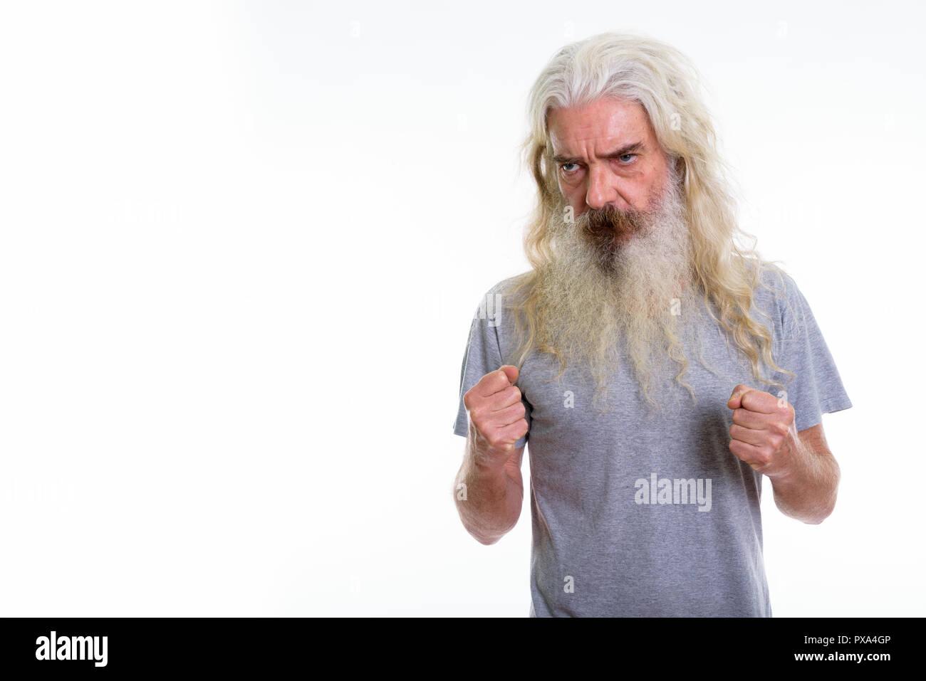 Studio shot of senior bearded man looking angry - Stock Image
