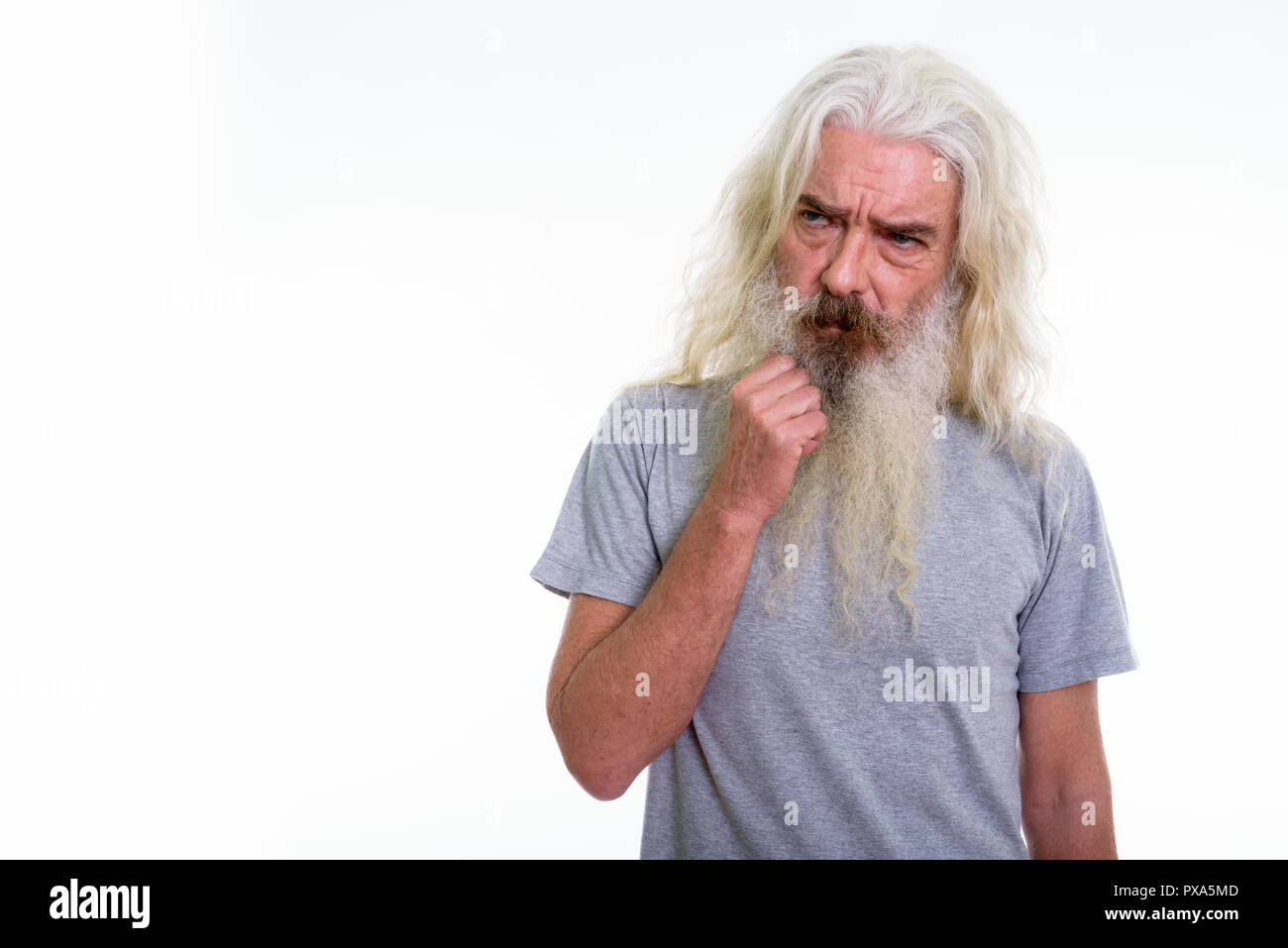 Studio shot of senior bearded man thinking while looking sad - Stock Image