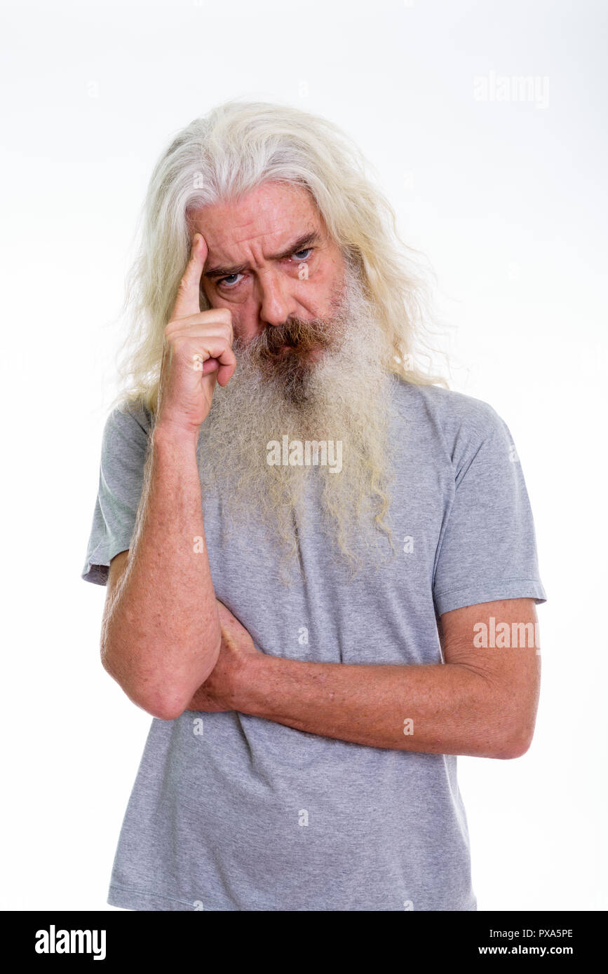 Studio shot of senior bearded man thinking with finger on head - Stock Image