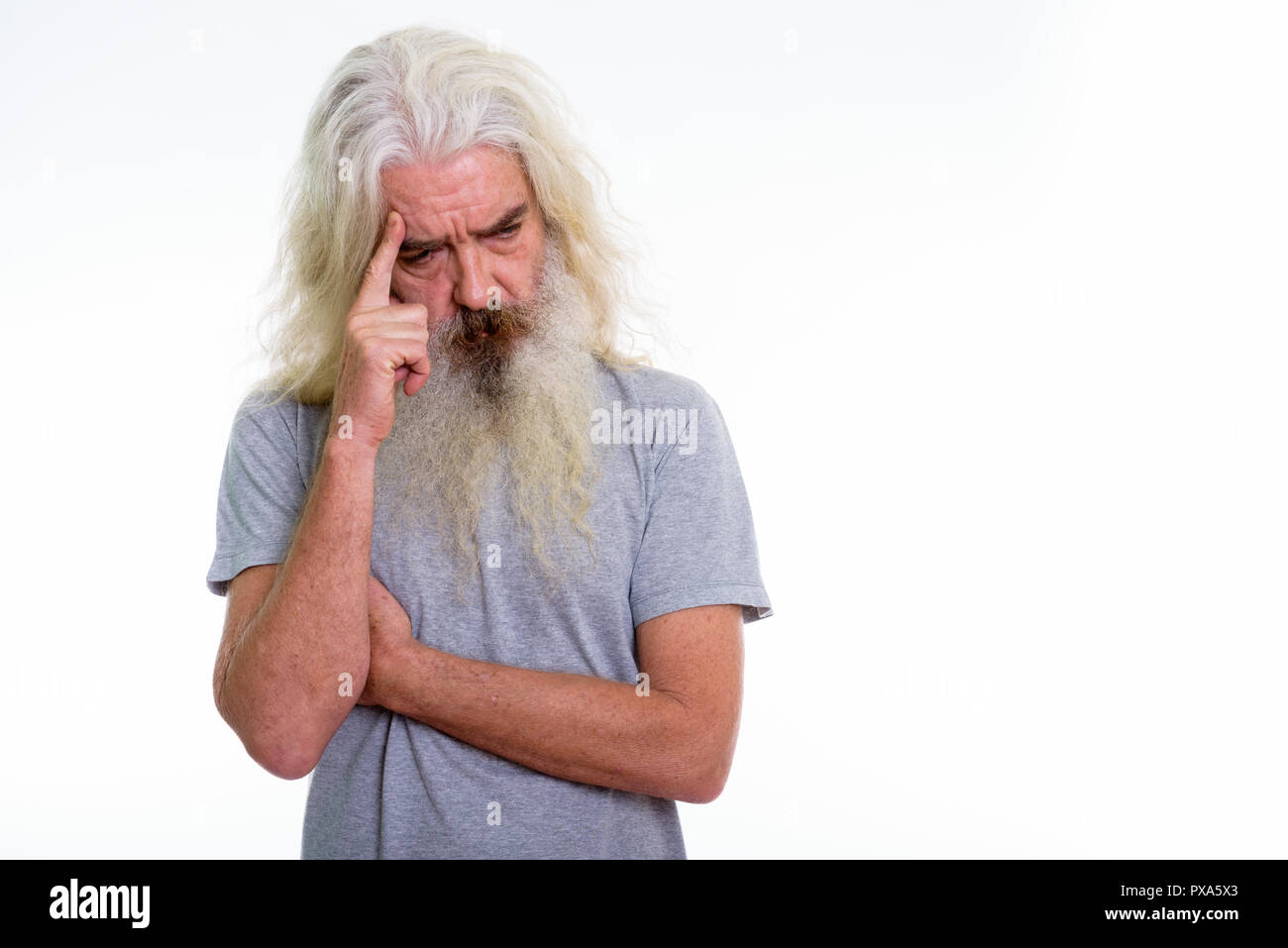 Studio shot of senior bearded man looking sad while thinking  - Stock Image