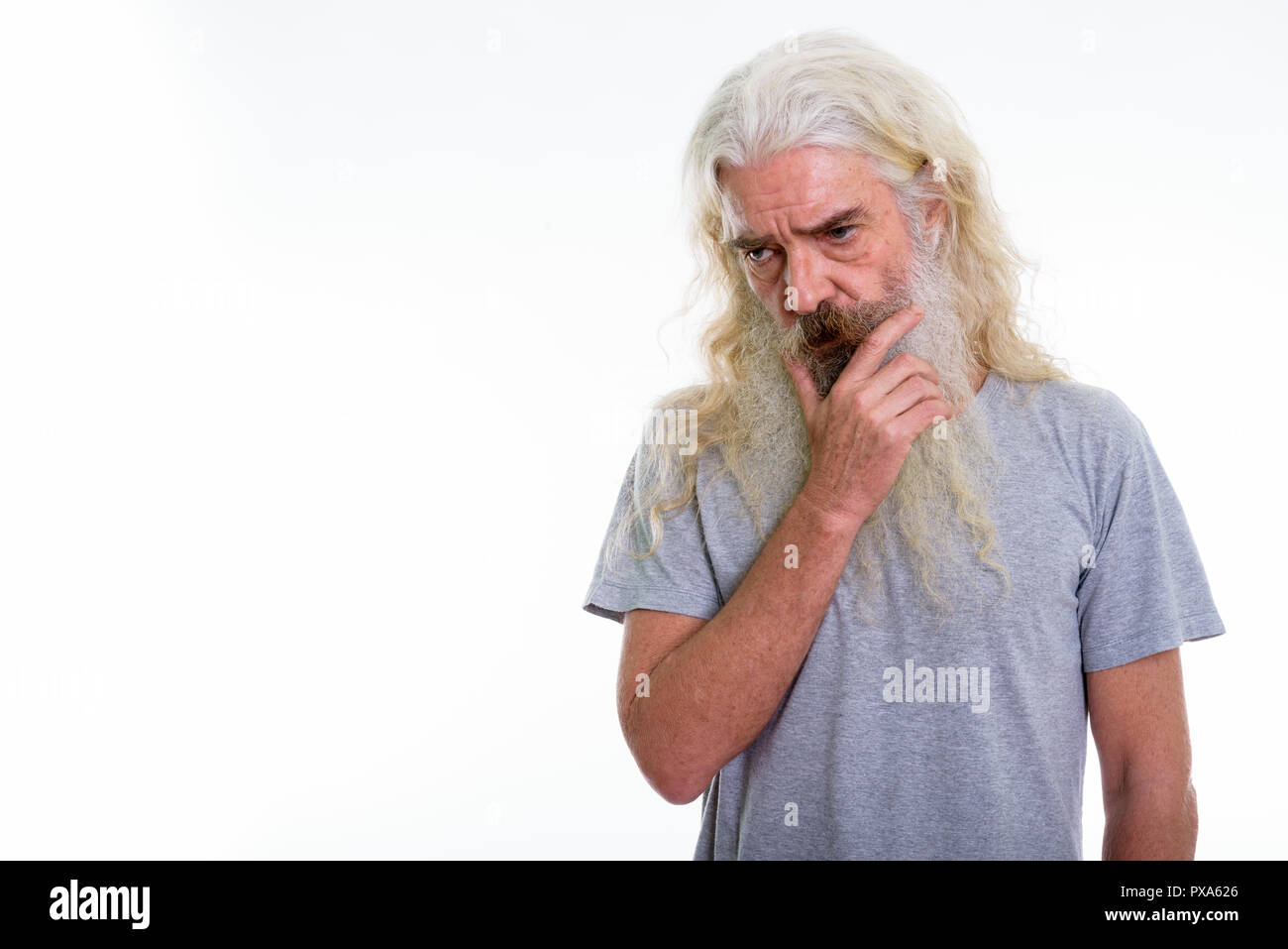 Studio shot of senior bearded man thinking while looking at dist - Stock Image