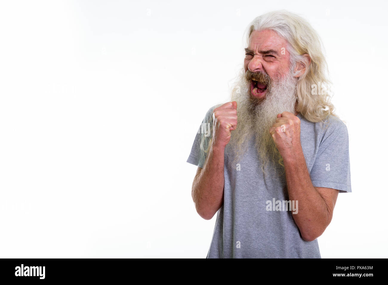Studio shot of angry senior bearded man screaming with both arms - Stock Image