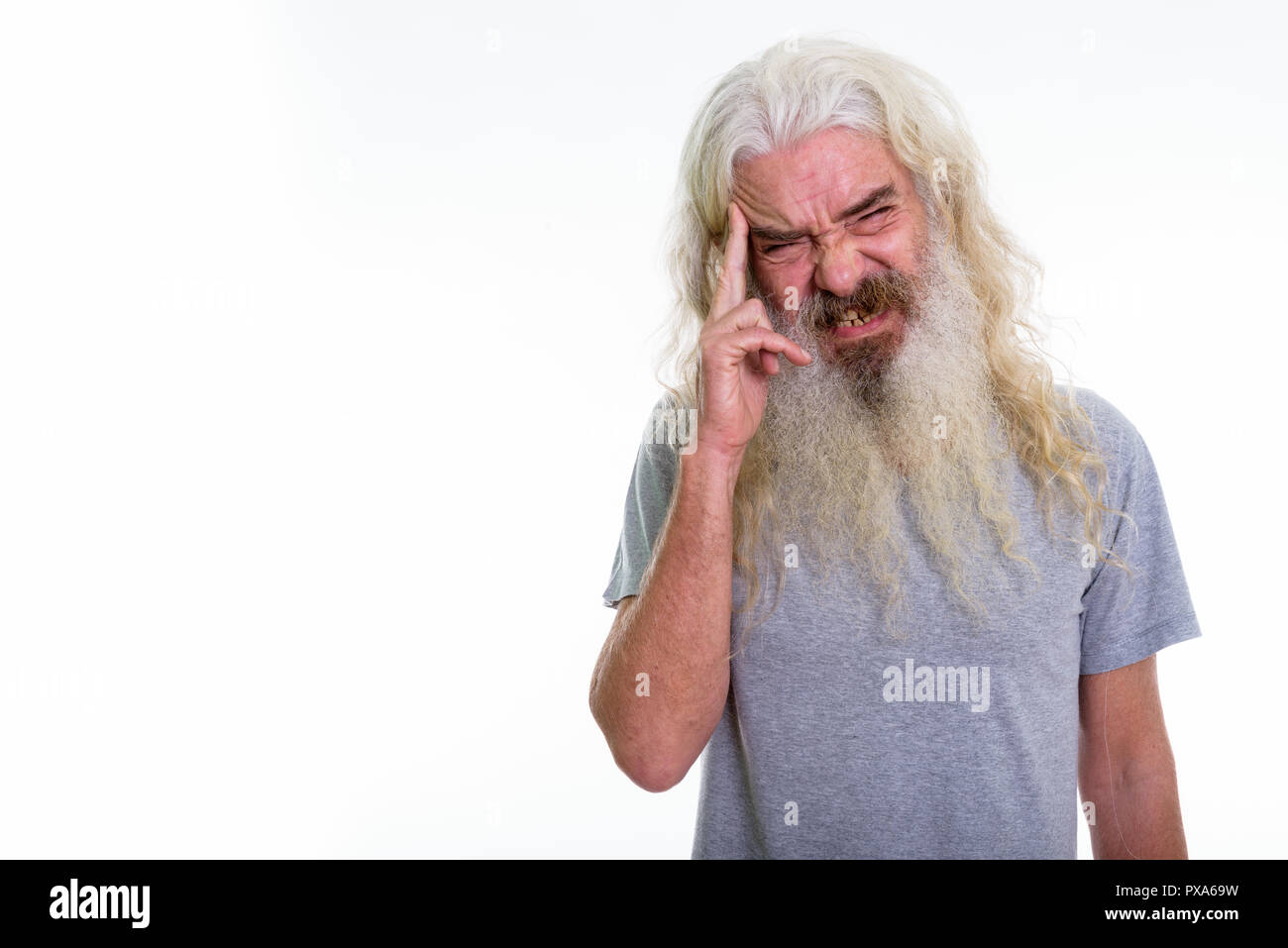Studio shot of senior bearded man having headache - Stock Image