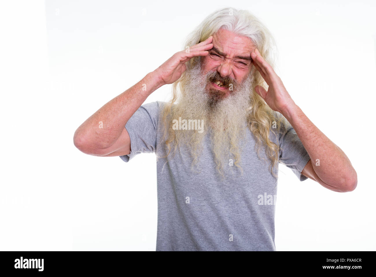 Studio shot of senior bearded man having headache with both hand - Stock Image