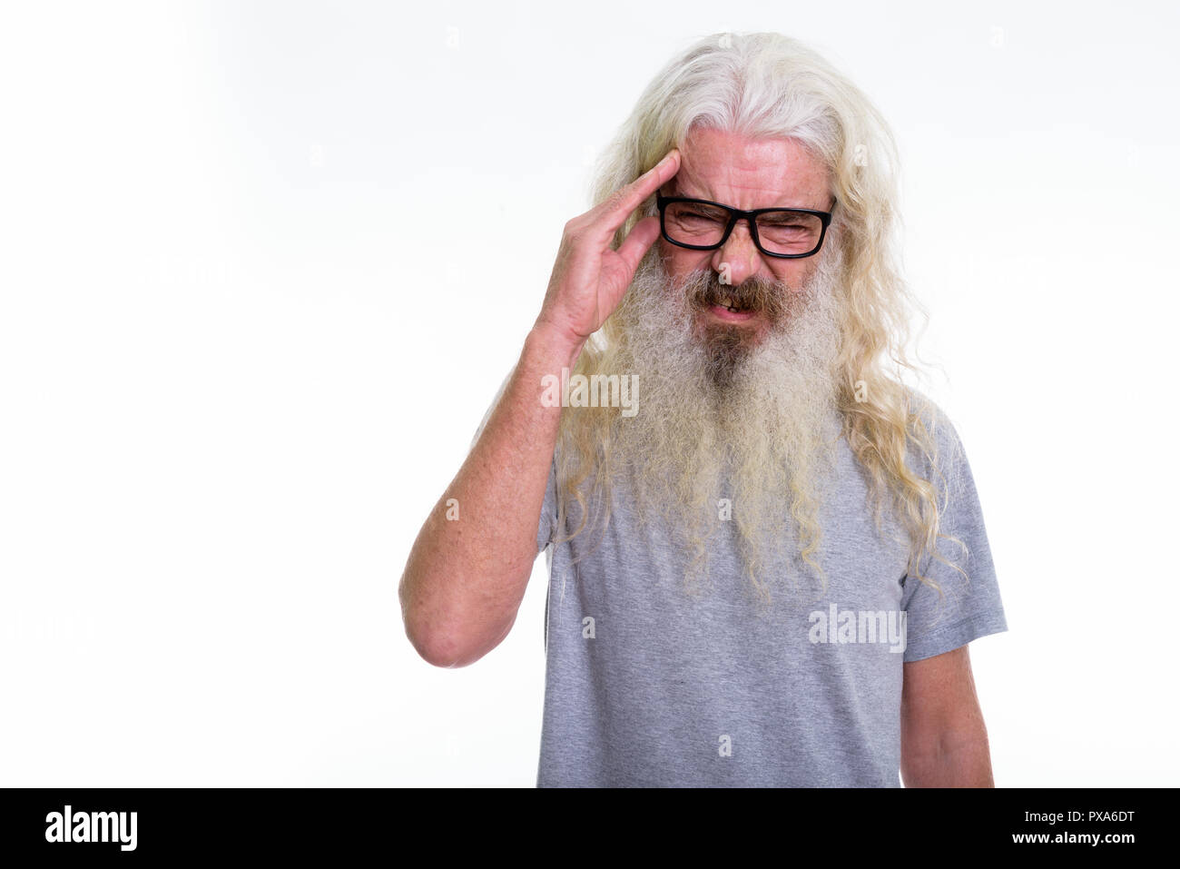 Studio shot of senior bearded man wearing eyeglasses while havin - Stock Image