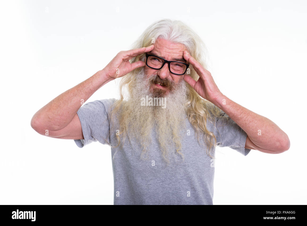 Studio shot of senior bearded man wearing eyeglasses while havin - Stock Image
