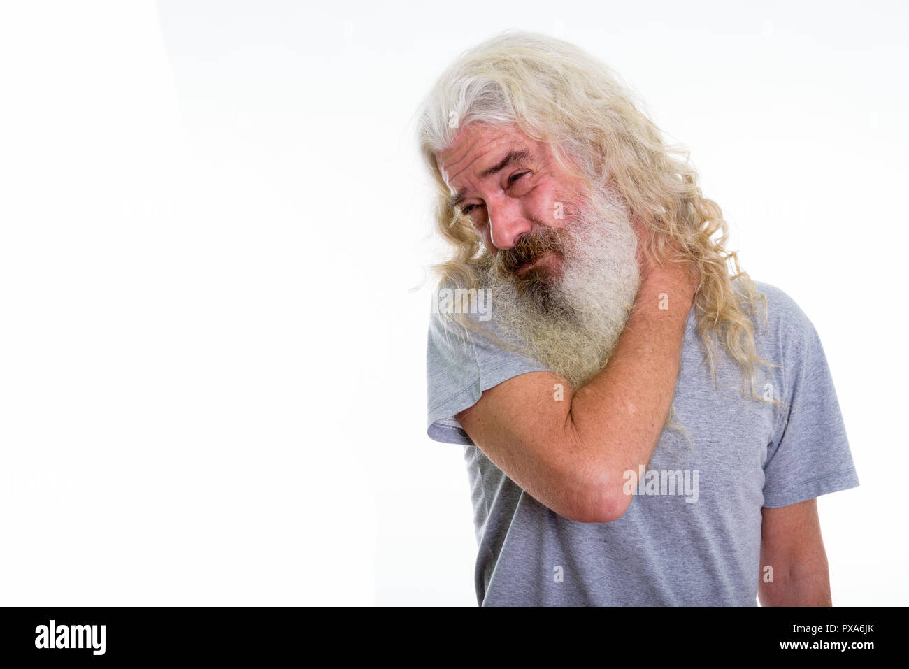Studio shot of senior bearded man having pain in the neck - Stock Image