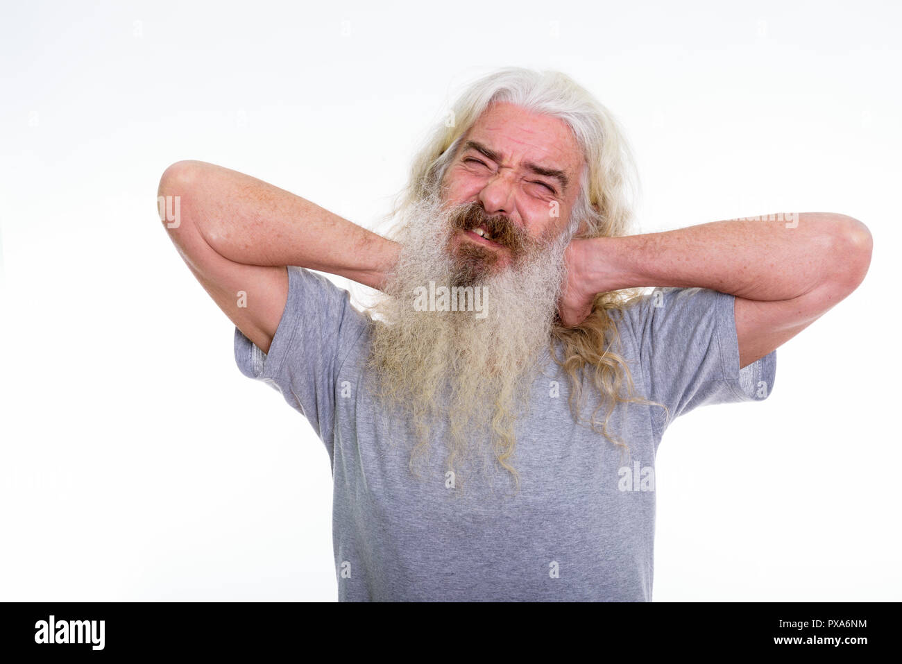 Studio shot of senior bearded man having pain in the neck with b - Stock Image