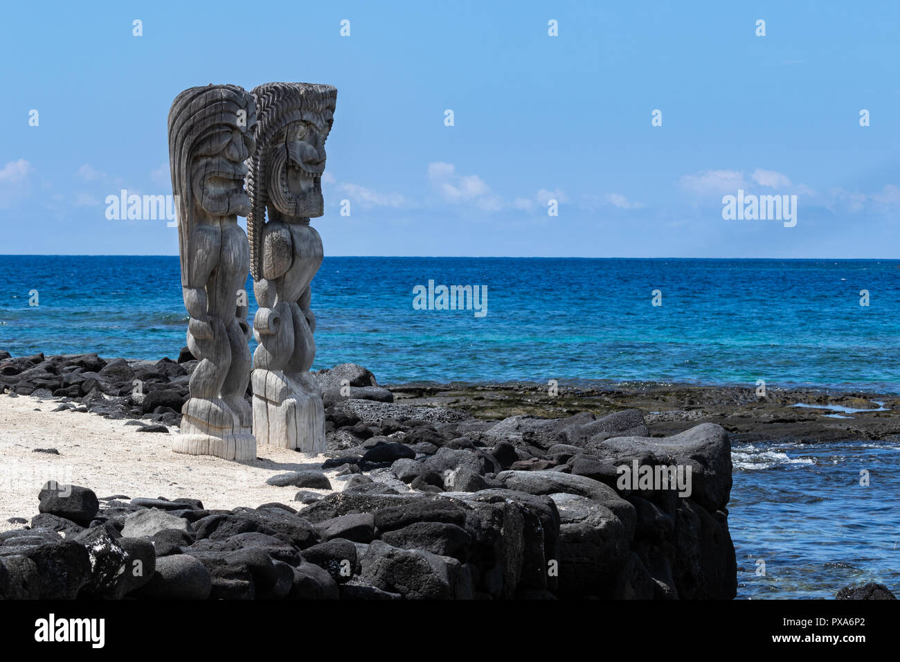 Pair of wooden status (Tikis), place of refuge (Honaunau), Hawaii. Standing on white sand, next to barrier wall of black lava rock. - Stock Image