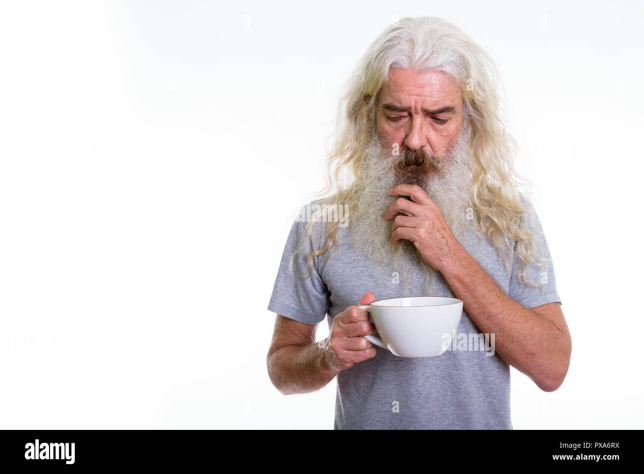 Studio shot of stressed senior bearded man thinking while holdin - Stock Image