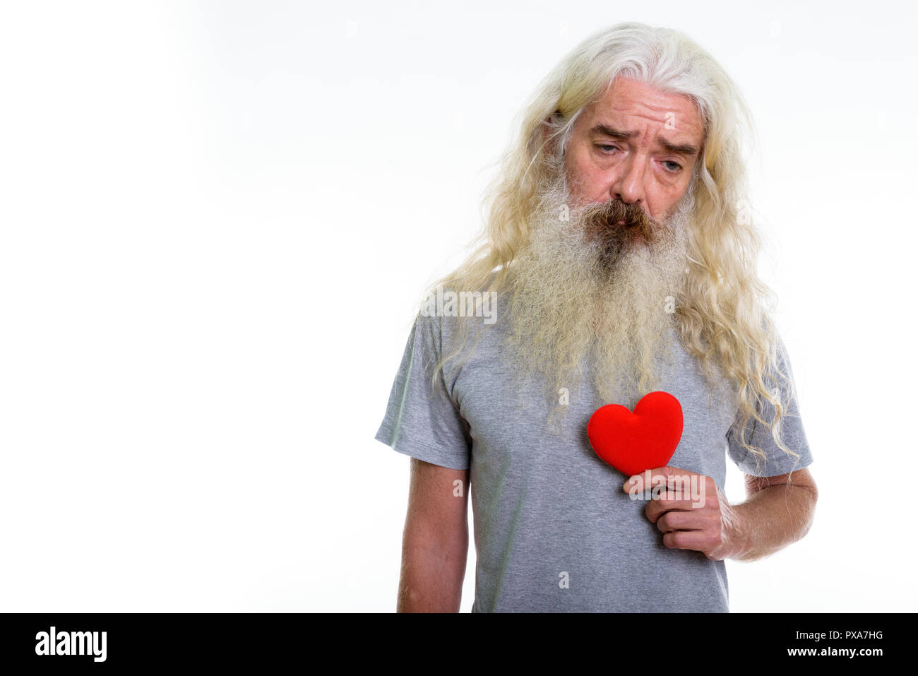 Studio shot of senior bearded man holding red heart while lookin - Stock Image