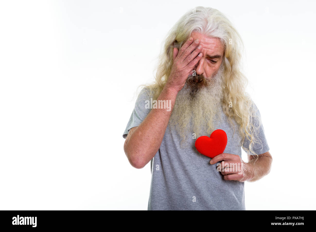 Studio shot of senior bearded man looking sad while holding red  - Stock Image