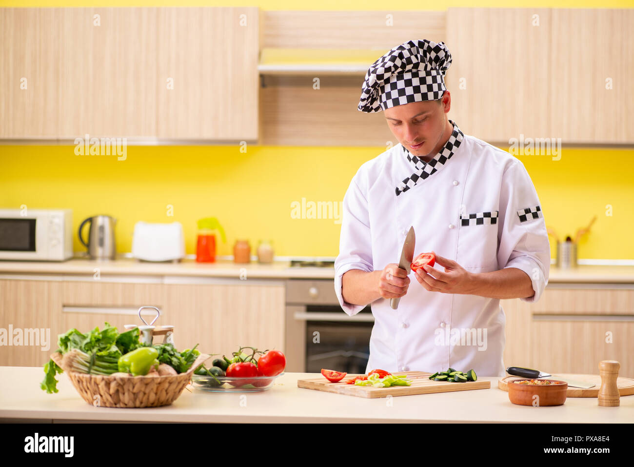 young professional cook preparing salad at kitchen stock photo