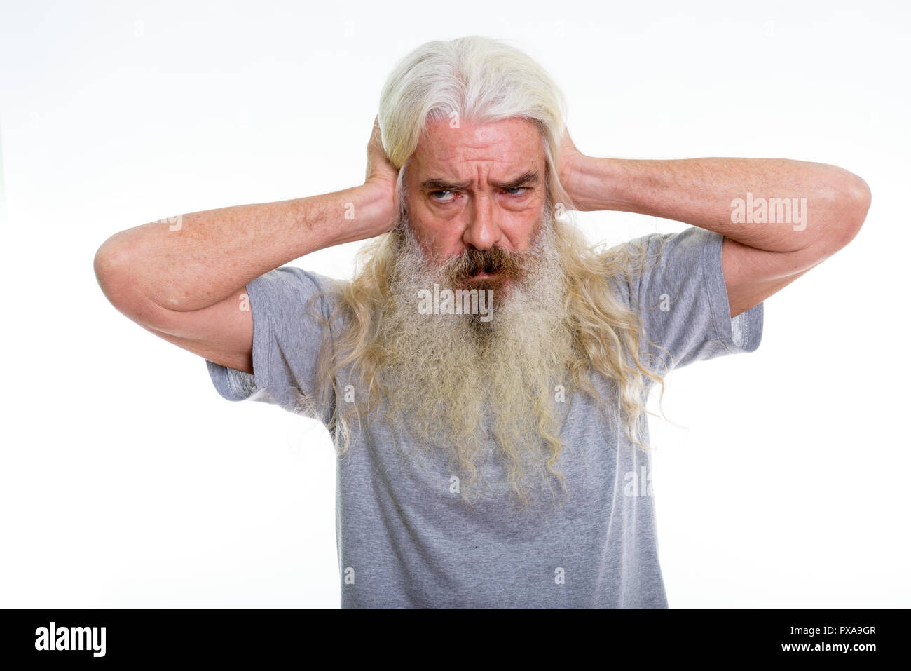 Studio shot of senior bearded man thinking while covering ears  - Stock Image