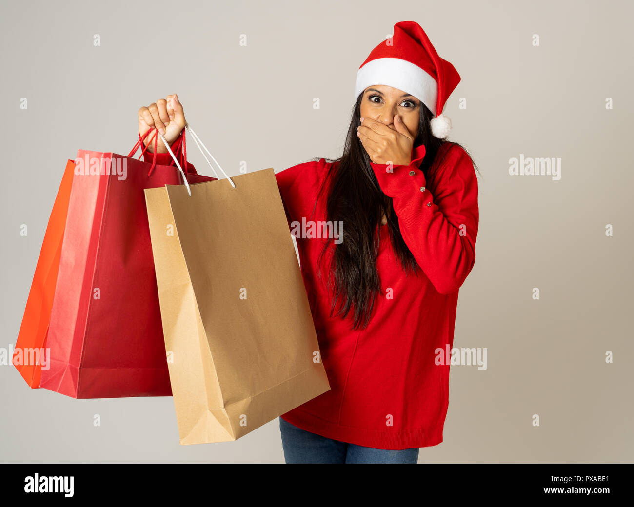 Young Woman Ready For Christmas With Paper Shopping Bags In Red And