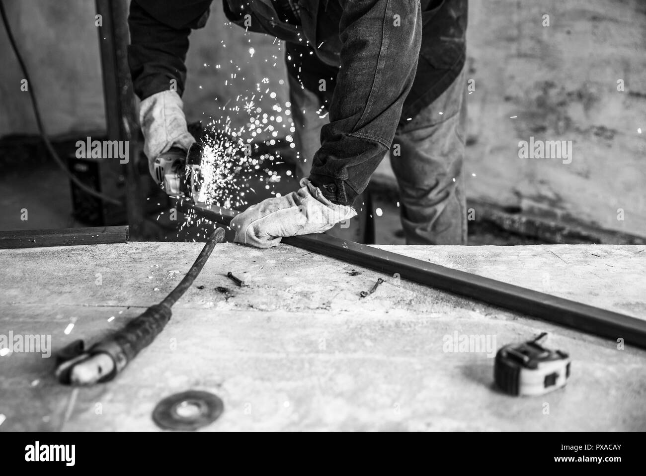 Worker cutting metal profile with electric angle grinder. People at work, profession. Monochrome effect - Stock Image