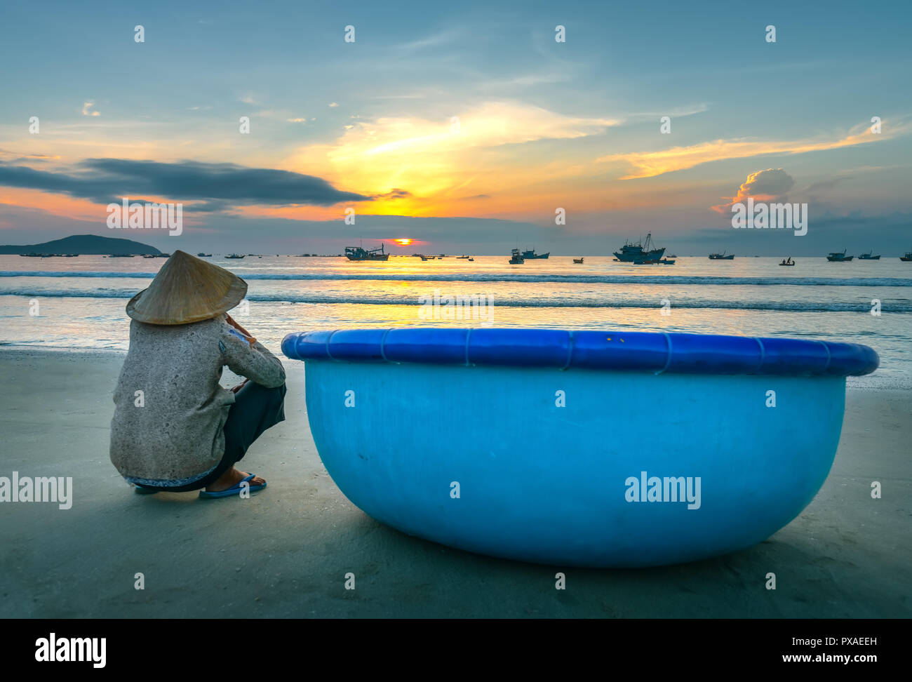 Old fisherman seated on a beautiful beach at dawn next to boat looking relatives fishing shore hoping for bumper harvest - Stock Image