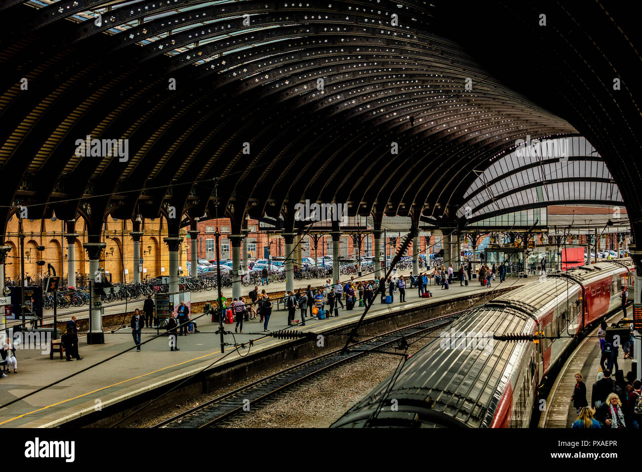 York, UK - Aug 28 2018: York Railway Station curved architectural details and station platform with trains and commuters - Stock Image