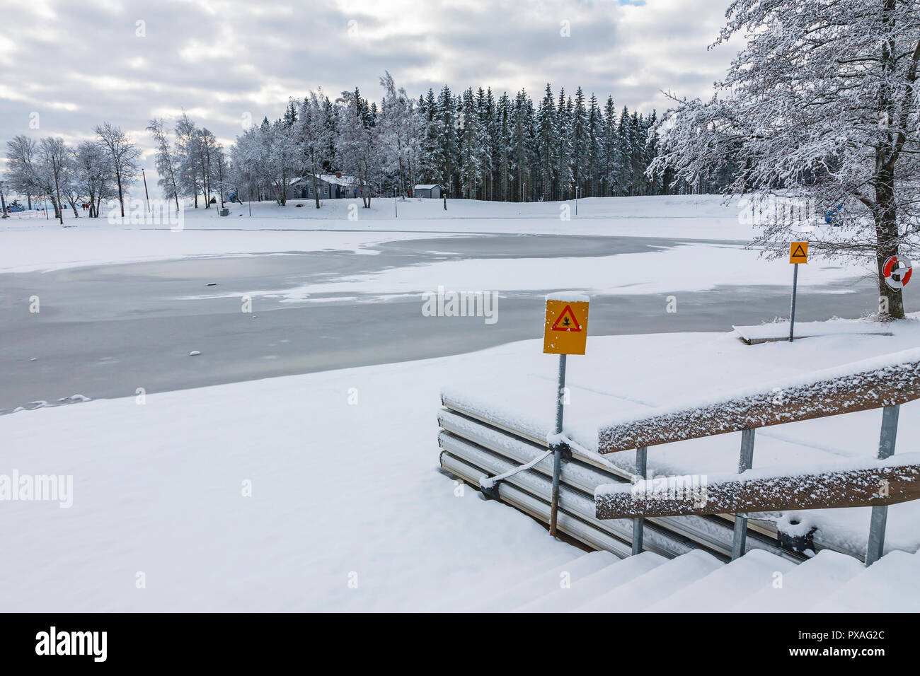 Ice covered lake with a warning sign for thin ice - Stock Image
