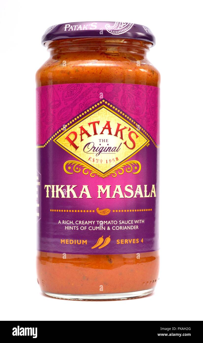 A glass jar of Pataks Tikka Masala,rich creamy tomato sauce with hints of cumin and coriander on a white studio background Stock Photo