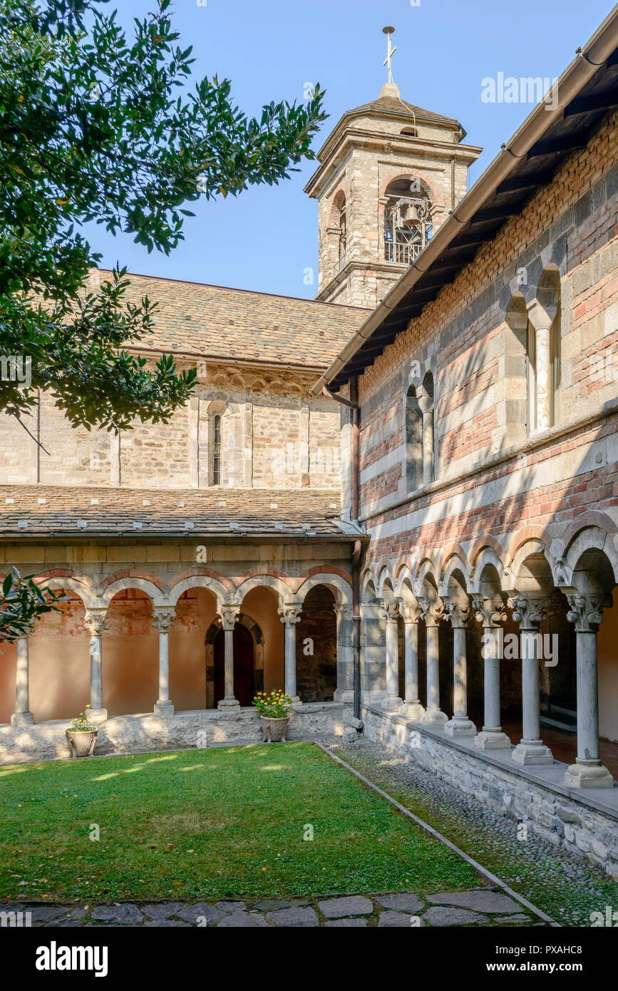 view of Romanesque cloister and belltower at Abbey on shore of Lario lake, shot in bright fall light at Piona, Lecco, Italy - Stock Image