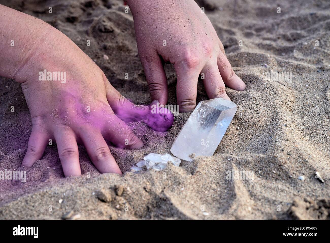 Hands playing in the sand with smoke bombs and crystals - Stock Image