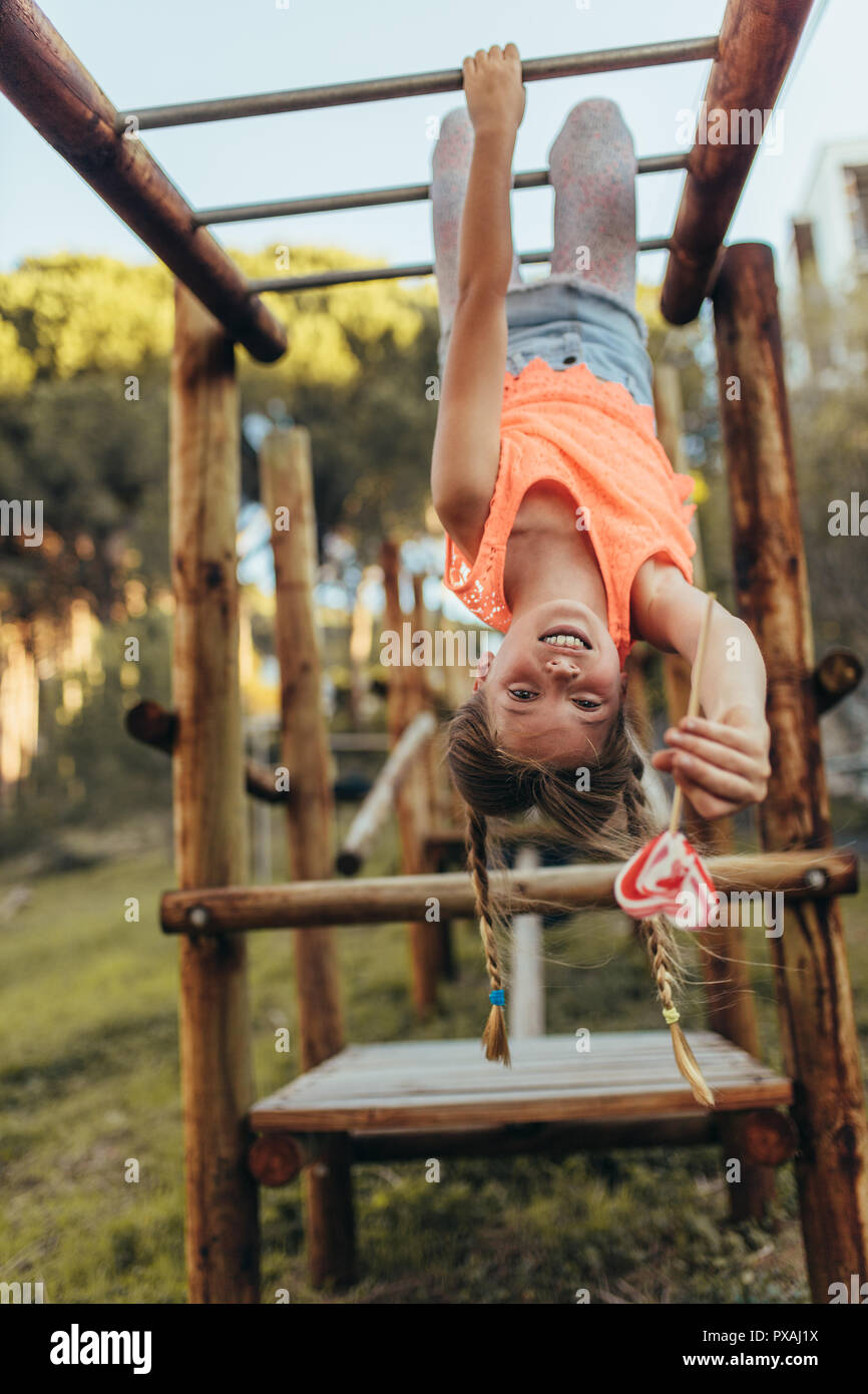 Girl hanging heads down in a park holding a heart shaped candy lollipop. Girl playing in a park hanging upside down on a horizontal ladder enjoying a  - Stock Image