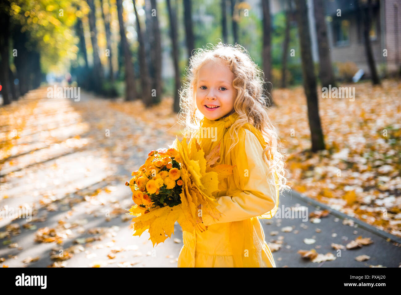 Little beautiful girl with blond hair in autumn background Stock Photo