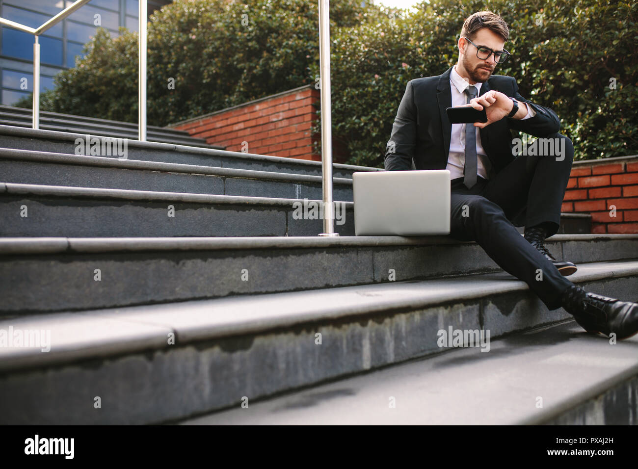 Business professional sitting on steps outdoors with laptop checking time. Young businessman waiting for someone outdoors. - Stock Image