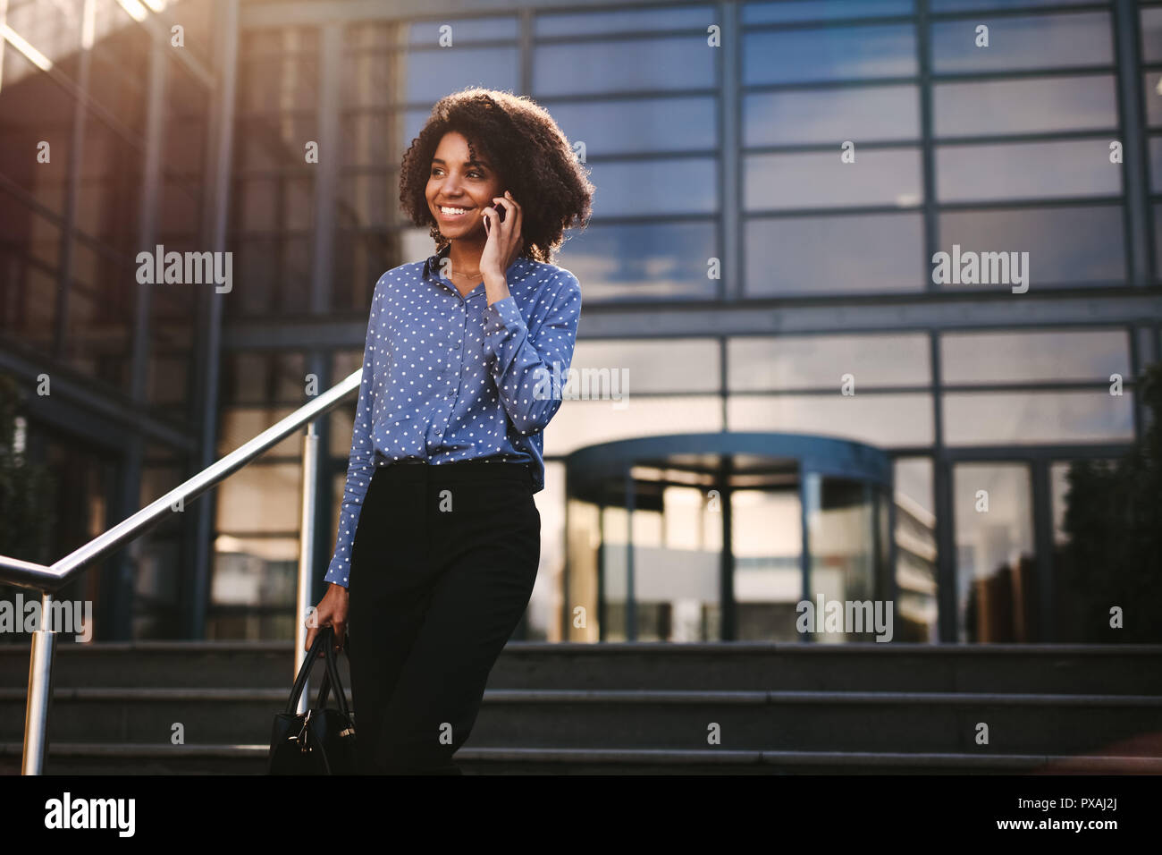 Woman walking down the steps outside office building and talking on mobile phone. Businesswoman talking on cell phone with office building in backgrou - Stock Image