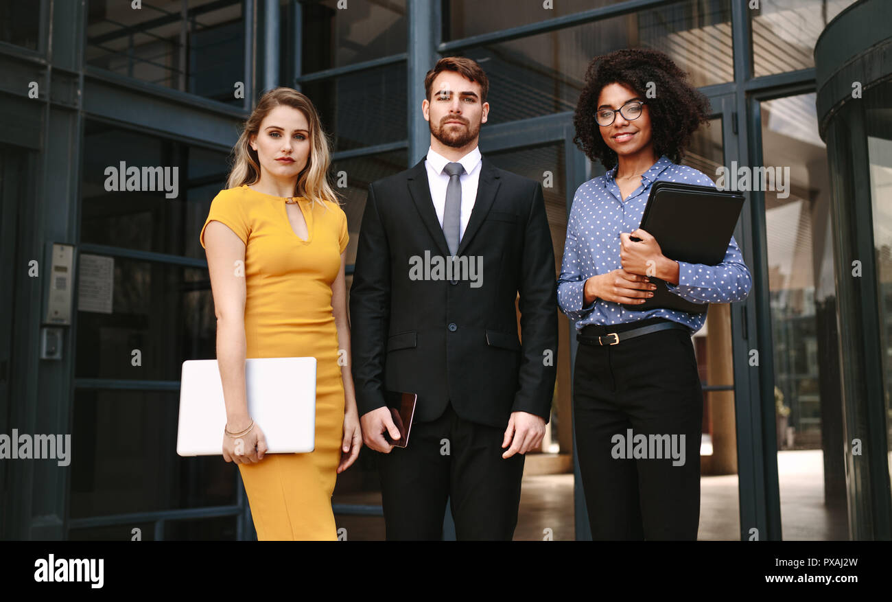 Portrait of three business people standing together in front of office building. Group of diverse business professionals looking at camera confidently Stock Photo