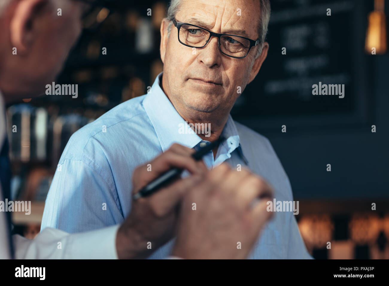 Senior man listening to the discussing of a male colleague in cafe. Business people talking over a new business plan while sitting in a restaurant. - Stock Image