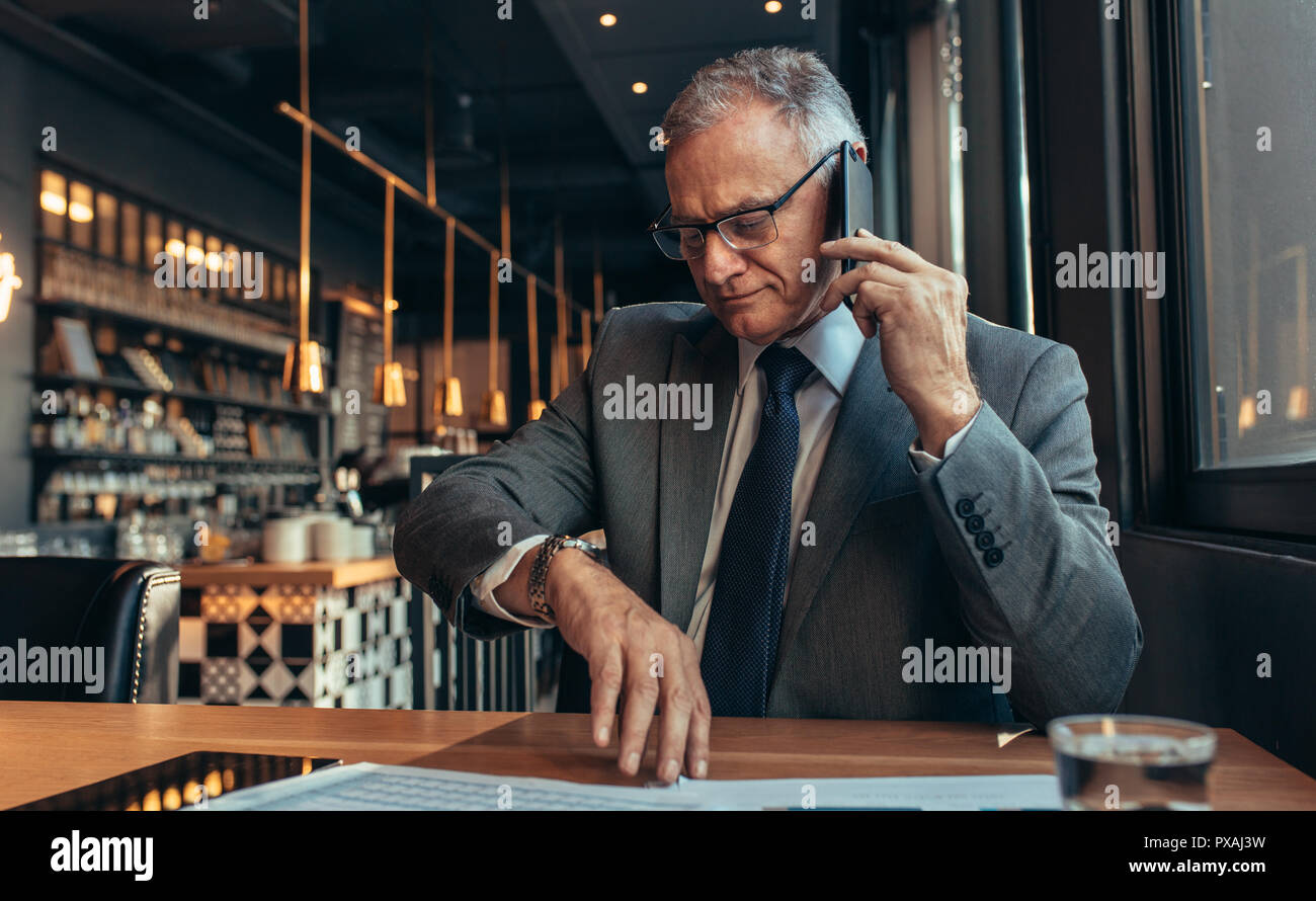 Senior businessman sitting at cafe making a phone call and checking time. Business professional waiting for someone at coffee shop talking over phone. - Stock Image