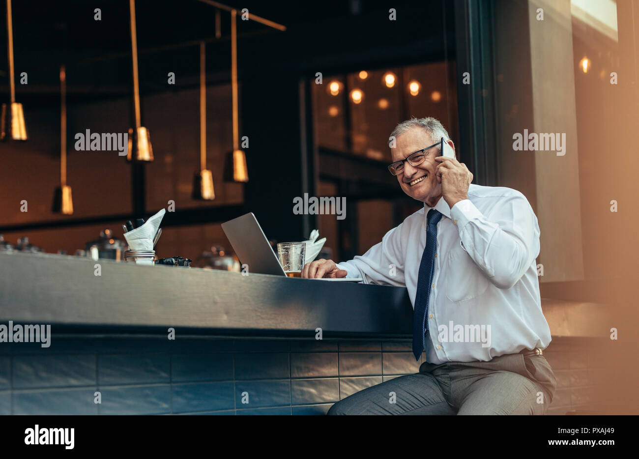 Smiling senior man in formal wear sitting at bar counter with laptop talking on cell phone. Happy mature entrepreneur making a phone call from bar cou - Stock Image