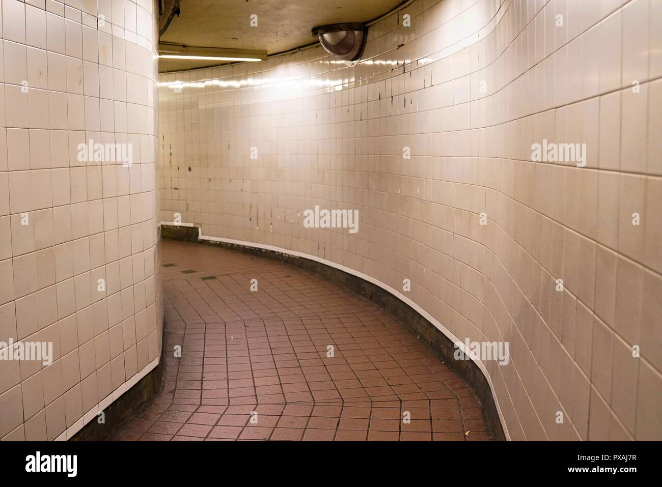 An Empty Hallway With White Subway Tiles On The Wall And Reddish - Tiles-for-the-hallway