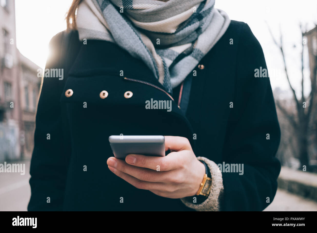 Young woman using smart phone outdoors on gray wall background. Female wearing big scarf, gold wrist watches, black coat and backpack holding mobile d - Stock Image