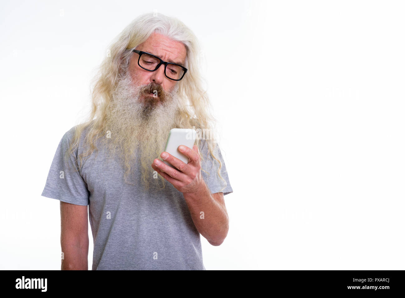 Studio shot of senior bearded man using mobile phone while looki - Stock Image