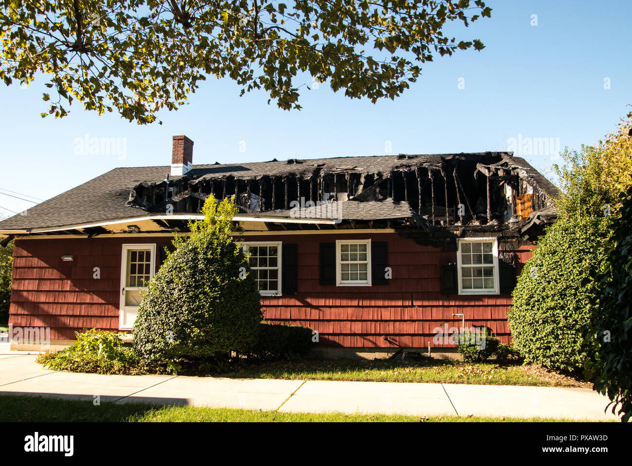 Small red house with roof and top floor destroyed by fire - Stock Image