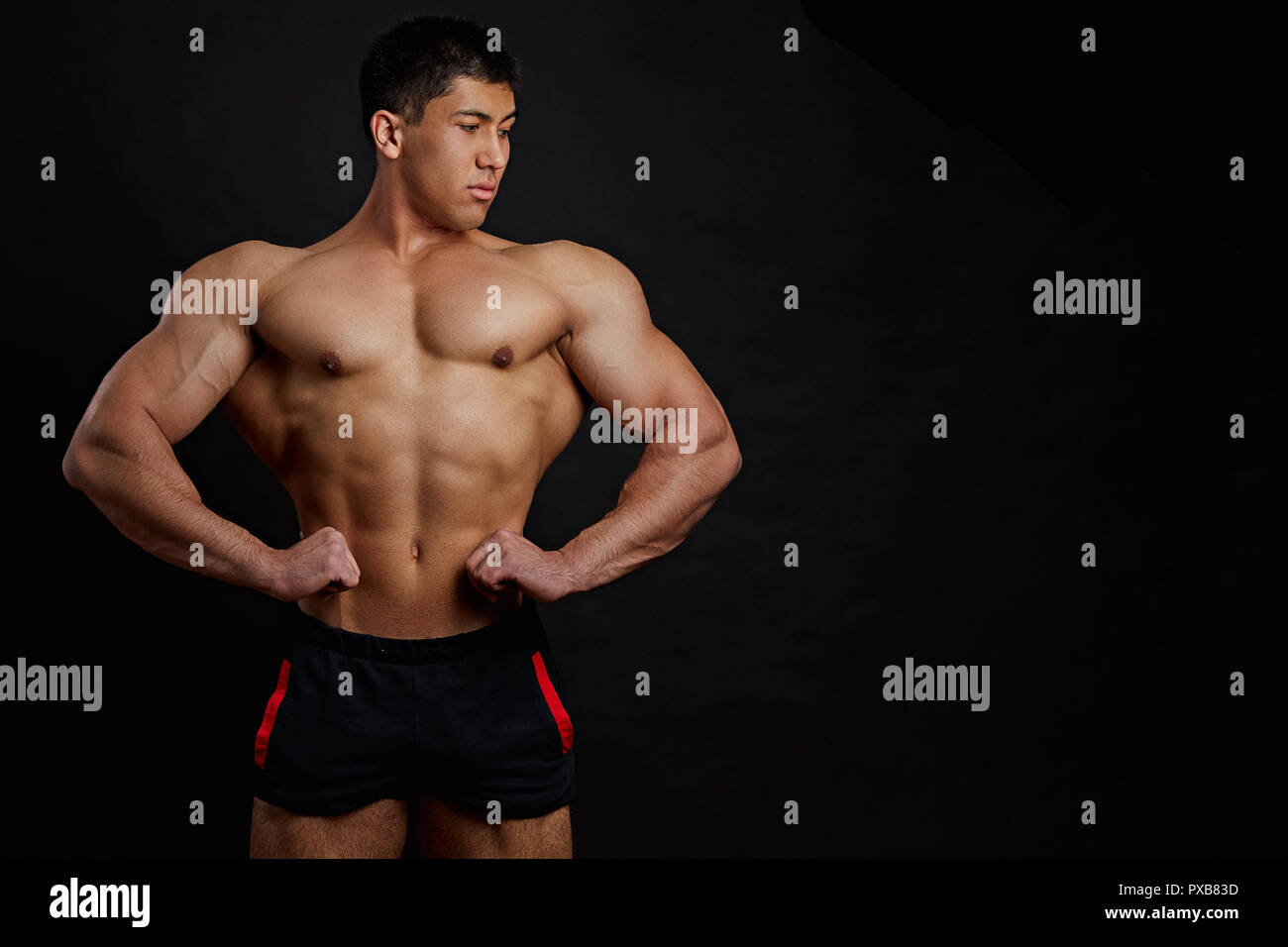 Asian bodybuilder is showing his muscles - Stock Image